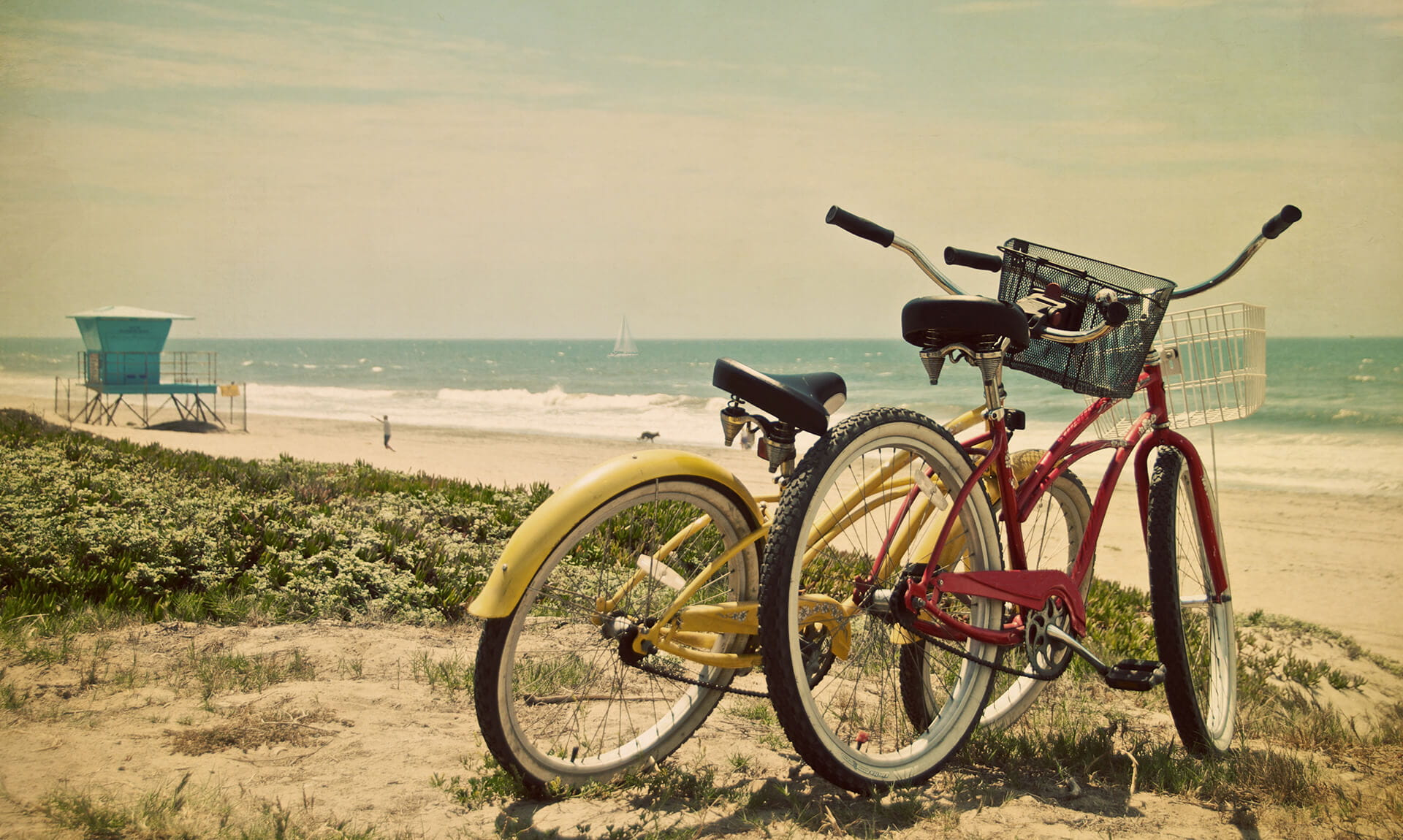 Yellow and red bikes on sand