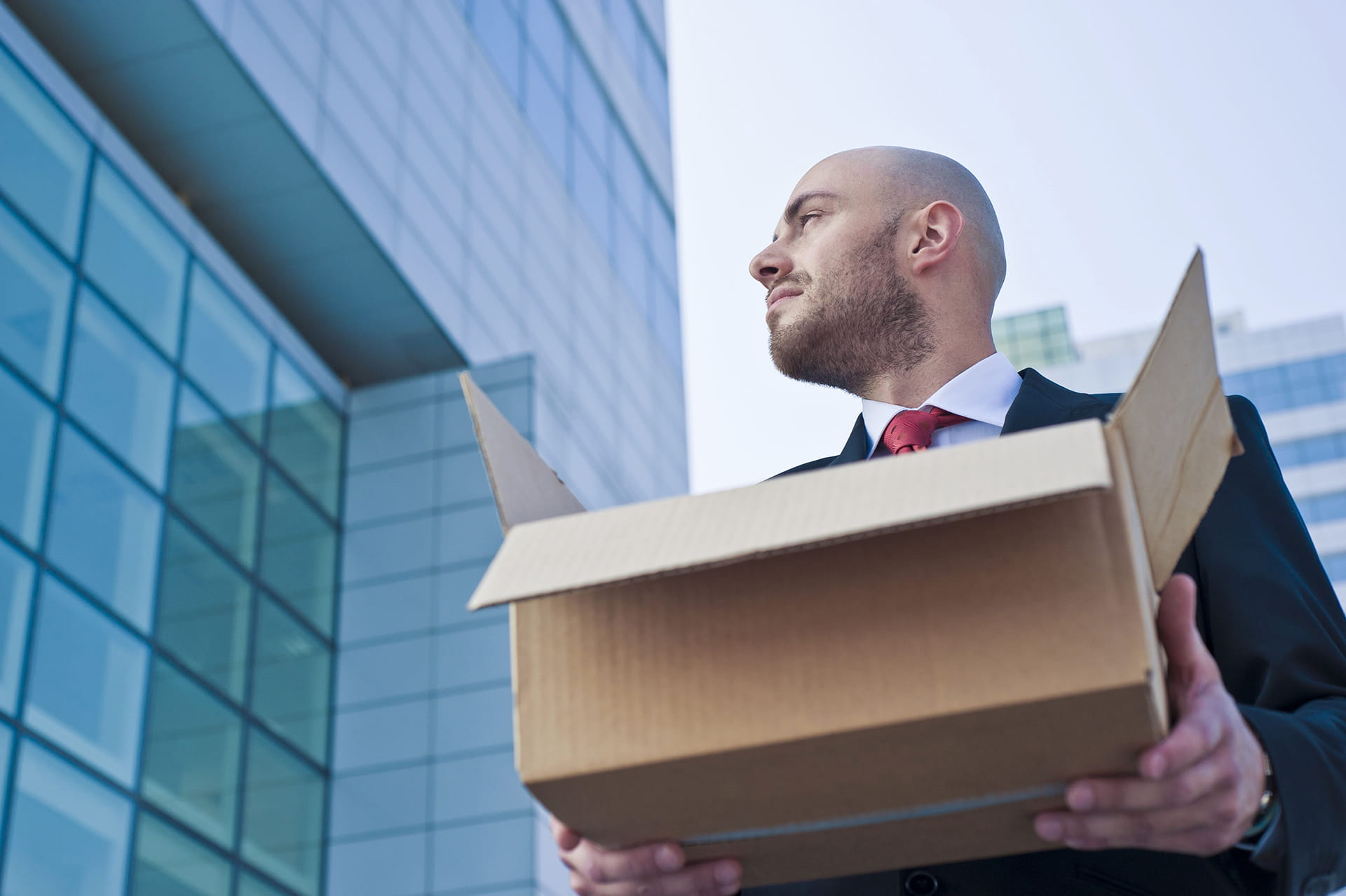 Young Businessman Holding A Cardboard Box Against Modern Skyscrapers