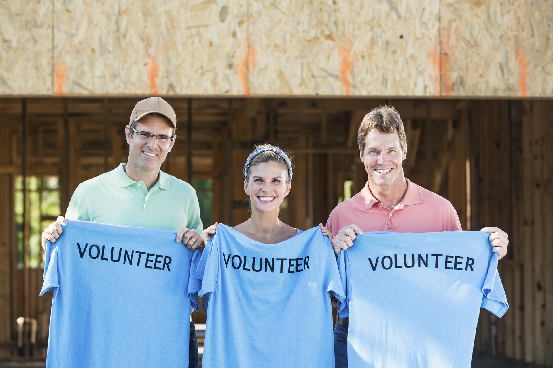 Three volunteers holding blue volunteer shirt