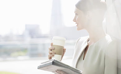 Woman holding a newspaper and a coffee