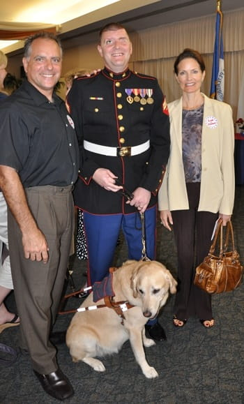 David and Kecia posing with a wounded veteran and his guide dog.