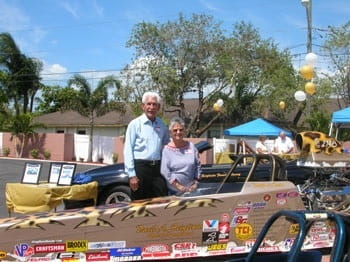 A man and woman posting behind a soapbox racecar.