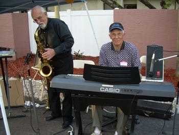 Two elderly musicians playing for the camera.