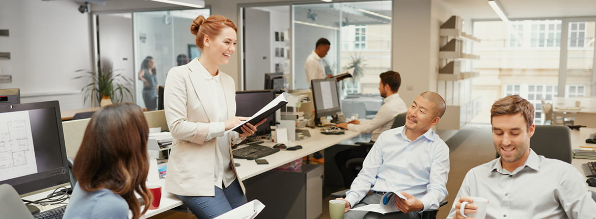 Attractive redhead woman stands discussing business with team sitting holding documents & mugs in casual meeting in open office