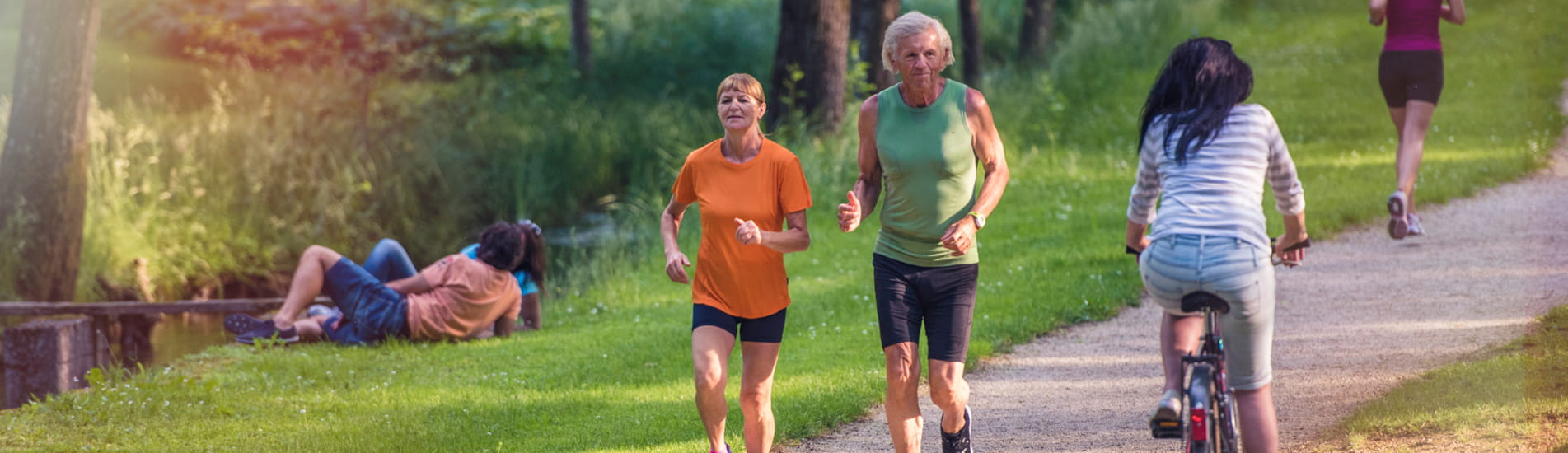 Two seniors running on a trail in a busy park.