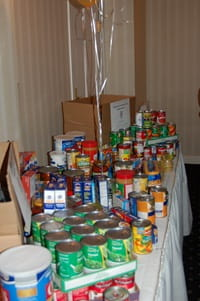 Various canned food items displayed on a table with a white tablecloth.