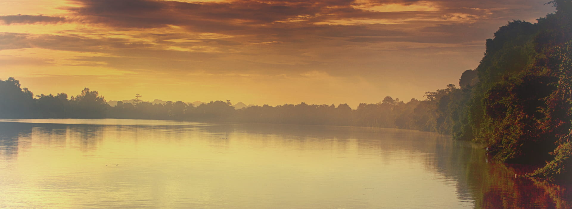A hazy lake at sunrise with an amber overcast.
