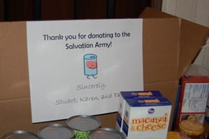 Salvation Army food box with various canned and boxed food items in front.