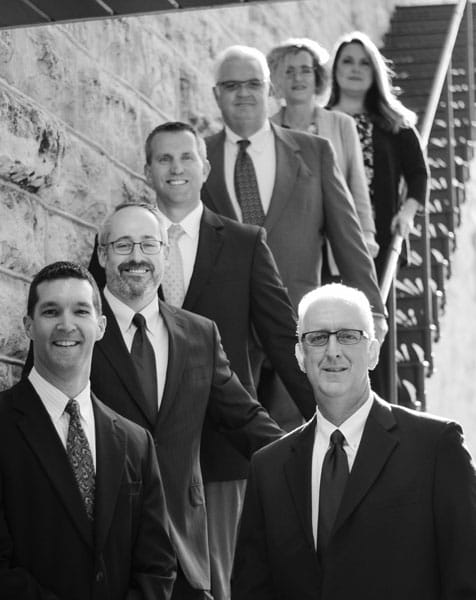 Goodwater Wealth Management Group team standing on stairs, photo is in black and white.