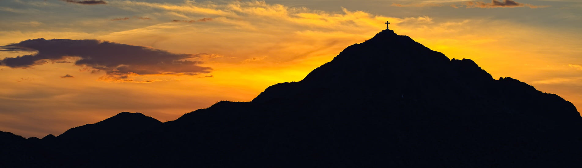 A mountain silhouette with a cross at the peak against an auburn sunset.