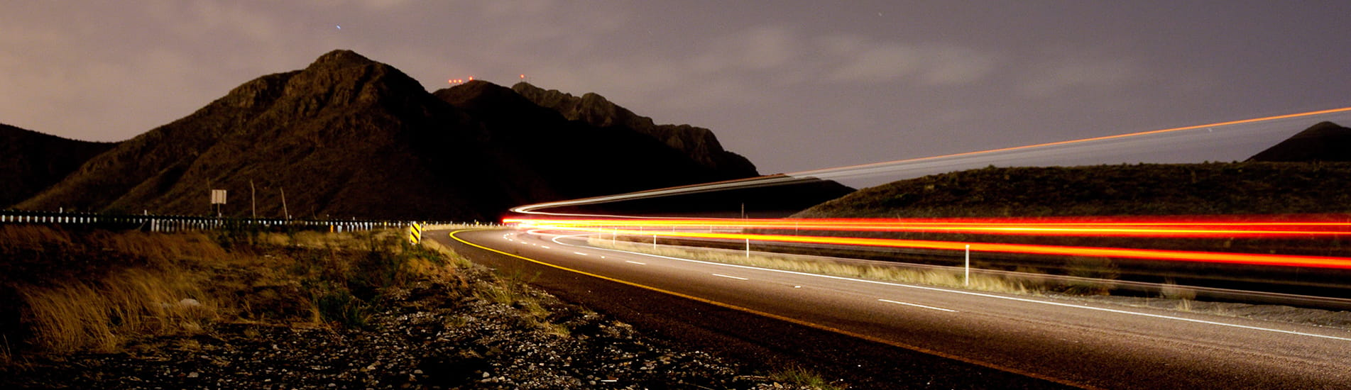 Highway at night with blurry lights and a mountain in the background.