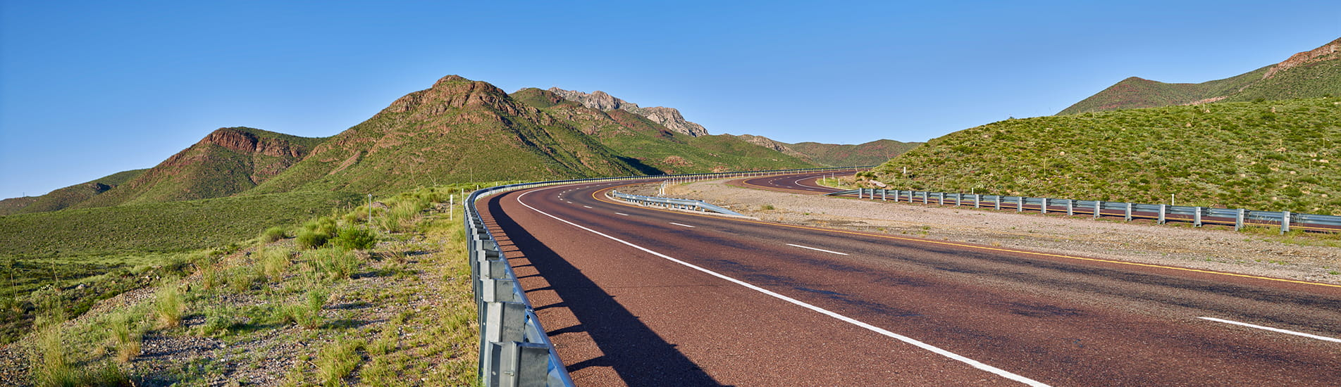 A highway road curving to the right set against a mountain range and clear blue sky.