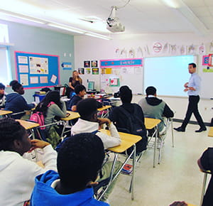 Jordan presenting at the North Miami Middle School during a financial literacy event to a class of 8th graders.