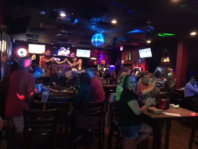 Crowd of people in darkened interior of sports bar