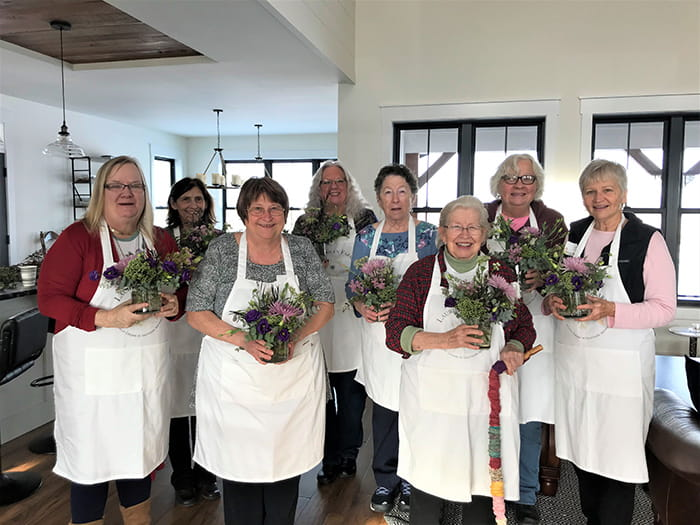Group of smiling women in aprons holding flower bouquets