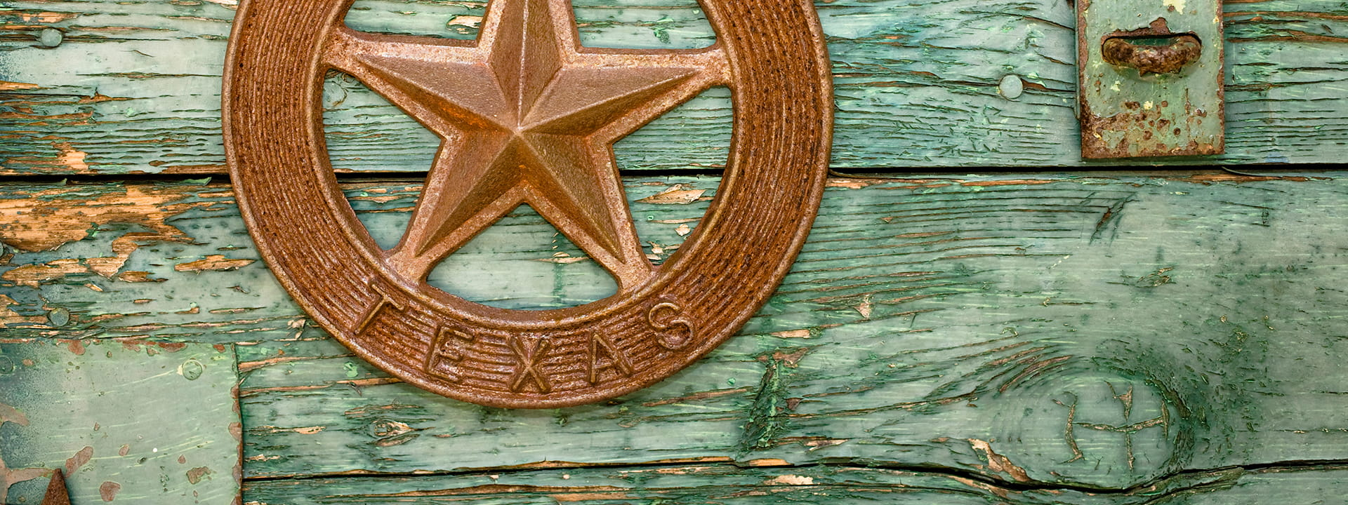 Texas badge on a wooden board.