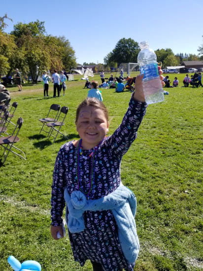 smiling girl holding bottle of water