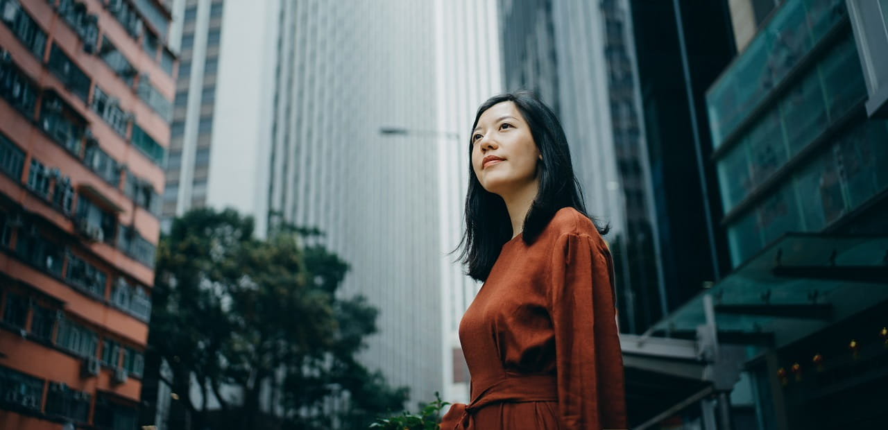 A young woman stands alone in front of a cityscape, looking up thoughtfully.