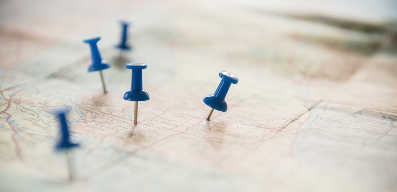 A close-up shot of blue thumbtacks pushed into a map.