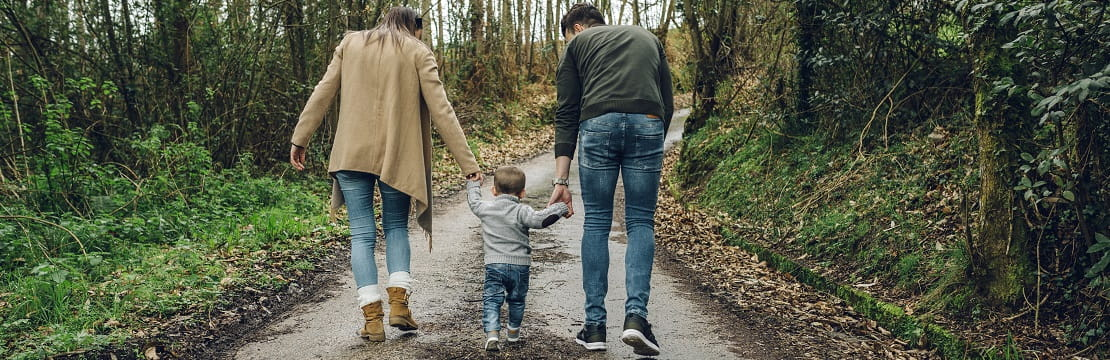A family walks down a nature path, their backs to the viewer. The parents hold the hands of a young child walking between them.