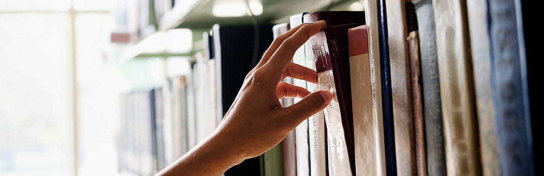 A hand takes one book off of a library shelf.