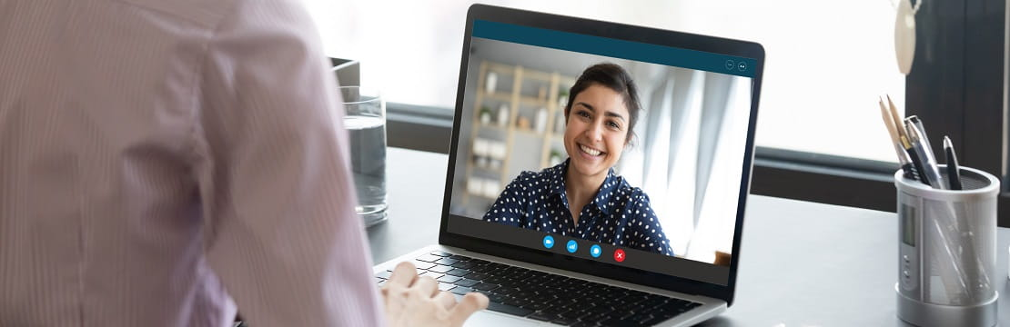 A young professional woman appears on a laptop screen as she attends a virtual meeting