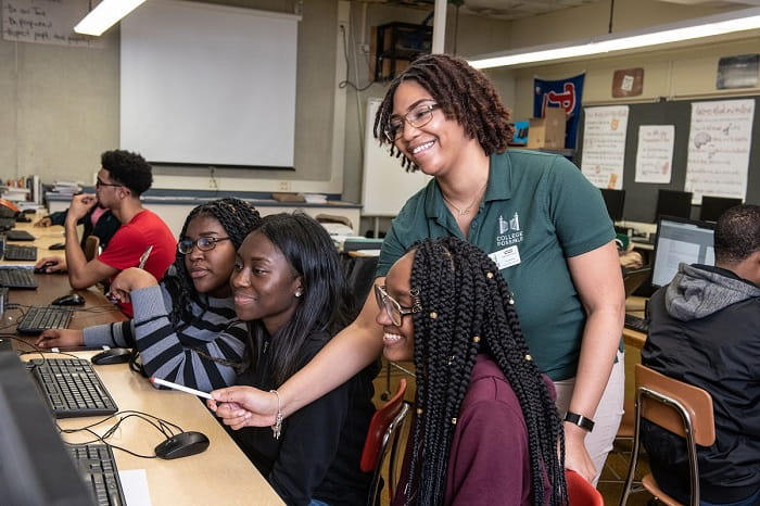 A smiling College Possible instructor with three high school girls in front of computers