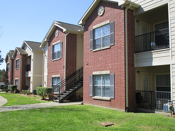 Red brick and tan sided, two-story apartment homes